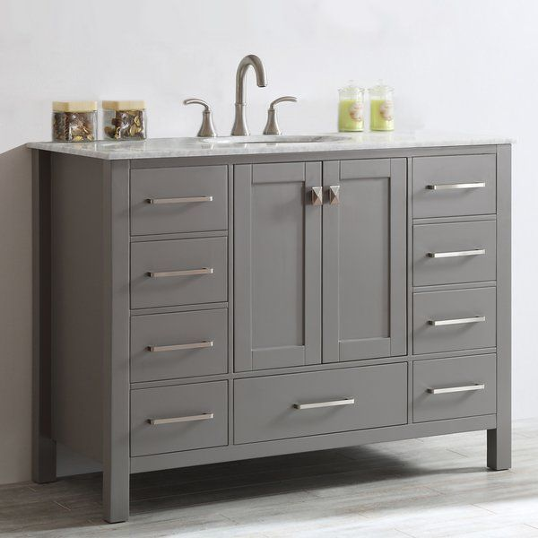 A perfect complement to a contemporary space, this vanity combines the clean, sharp lines of modern design with classic furniture styling. The carrara white marble countertop provides a dramatic contrast with the grey cabinet. Simple, bar-style pulls and knobs adorn the spacious drawers and doors, which conceal ample storage space for all your bathroom accoutrements.
