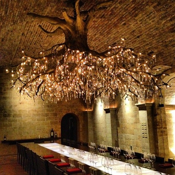 Candelabro con cristales y luces en base de árbol.