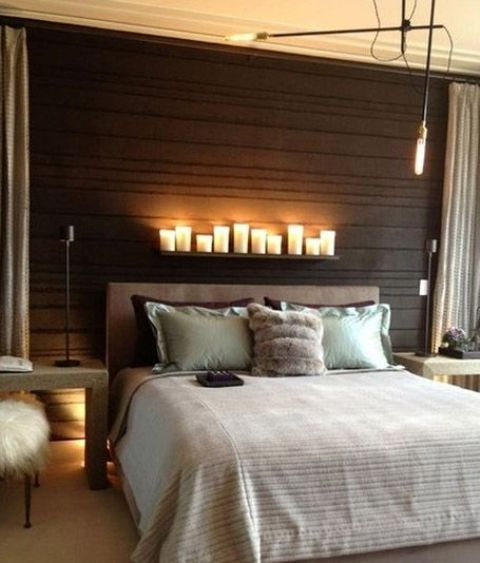 small LED lamps and pillar candles on the shelf above the bed