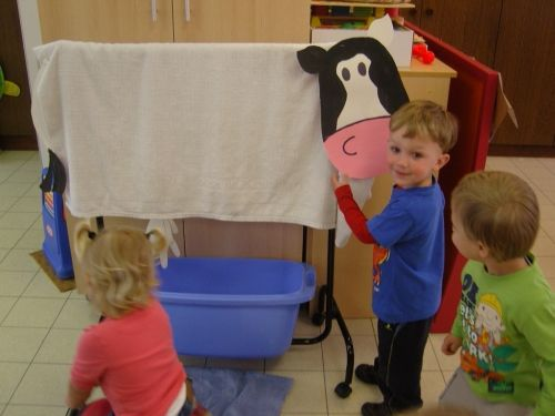 Love this simple cow. Make a cow head and wrap a white blanket around a shelf or furniture. Attach a glove with tiny holes at each finger below the blanket and fill with water. Add a plastic container and let children milk the cow.