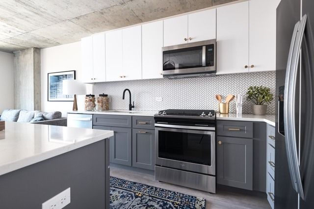 Modern Kitchen With Concrete Ceilings White And Grey Cabinets Stainless Steel Appliances Plank Flooring Wh White Kitchen Trendy Kitchen Kitchen Countertops