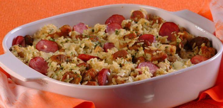 250 g de pernil cortado em cubos pequenos e temperado a gosto   - . ½ peito de frango em cubos pequenos temperados a gosto   - . 2 gomos de linguiça toscana em rodelas   - . 2 colheres (sopa) de óleo ou azeite   - . 1 cebola média picada   - . 2 dentes de alho bem picados   - . ½ xícara (chá) de polpa de tomate   - . 2 xícaras (chá) de arroz cru   - . 5 xícaras (chá) de água fervente   - . Sal a gosto   - . 2 colheres (sopa) de salsa picada   - . 1 xícara (chá) de queijo meia cura em…