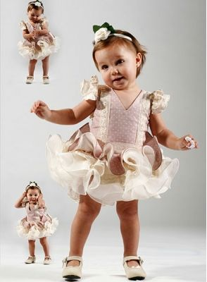 Trajes de Flamenca para Bebe confeccionado en hilo de color rosa palo con lunares en beige, es un traje de gitana corto con tres volantes el primero es igual que el vestido y dos volantes con motivos de encaje y organza. cuenta con tiras bordadas en el cuerpo del vestido de flamenca y antes de empezar los volantes, las mangas son de sisa cons dos volantes. #trajesdeflamencaniña http://www.elrocio.es/trajes-de-flamenca-nina/2232-trajes-de-flamenca-bebe.html