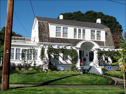 Very dignified Dutch Colonial. It's very symmetrical with a pergola on either side of the barrel-vaulted porch roof.  And the sun room. Very 1920s. For more information about Dutch Revival and other American residential house styles of the 20th century, see Antique Home & Style.