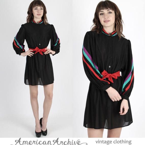 "Vintage 80s boho secretary mini dress.  Button front bodice with puff sleeves.  Gathered elastic waist with draped skirt.  Sheer black and rainbow striped poly.  You may need a slip. size estimate: M shoulders: 15 bust: 40 waist: 24-40 hips: - total length: 33.5""     Model is 59 and measures 32 bust, 24 waist, 35 hips Belts and other accessories are not included."