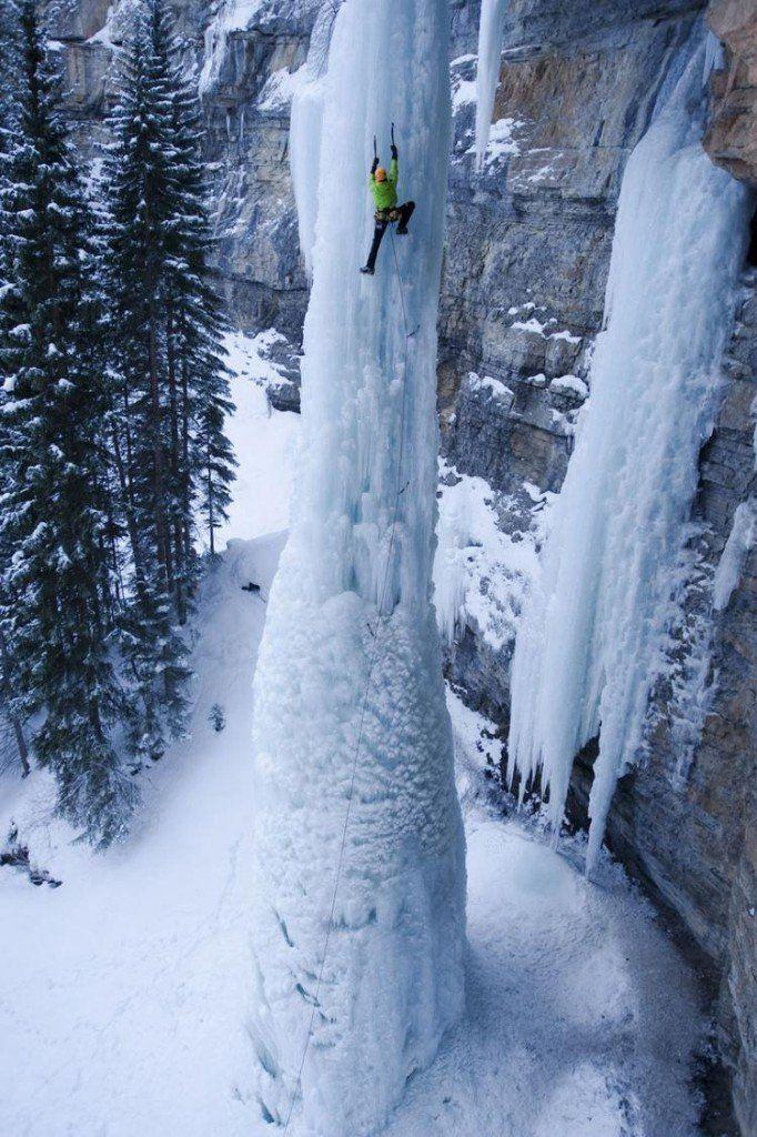 Hombre escalando una catarata congelada.