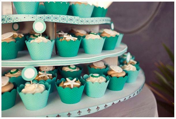 Wil je geen traditionele bruidstaart? Ga dan voor een  bruidstaart bestaande uit verschillende cupcakes! Deze  in strand thema is perfect voor een zomerse bruiloft op het strand!