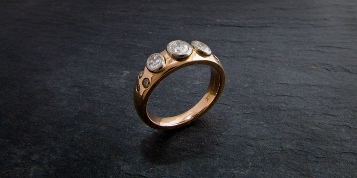 A rose gold ring with oval diamonds set in white gold with cognac diamond shoulders