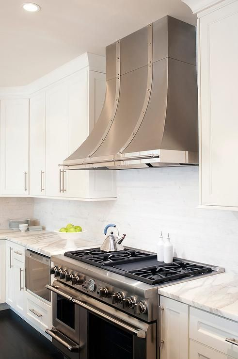 A stainless steel French kitchen hood accented with rivet straps stands over a stainless steel stove.