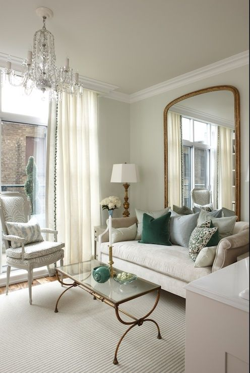 Living room with soft green paint color, antique gold floor length mirror, Sarah Richardson Design Nicole Sofa, green pillows, antique brass and glass coffee table and white cornice box with floor to ceiling ivory curtains.  Sarah Richardson Design House Beautiful: The Elegant Home | ZsaZsa Bellagio - Like No Other