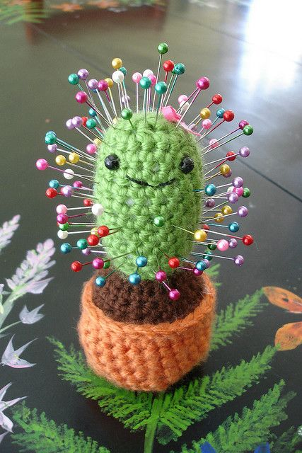 Tiny Ami Cactus Pincushion By Ana Paula Rimoli @ravelry: Hook: 4.0 mm (G). Yarn: Red Heart Soft Yarn Solids. Notes~Filled bottom with old glass beads to weight it.