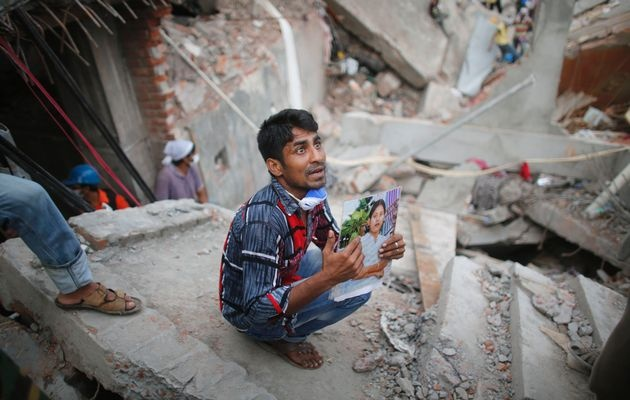 Horror in Bangladesh | A relative holds up a picture of a garment worker in front of the rubble of the collapsed Rana Plaza building, in Savar, 30 km (19 miles) outside Dhaka.  Photo: ANDREW BIRAJ / REUTERS