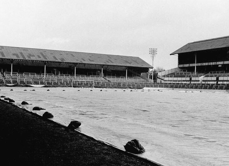 A frost cover held down with stones protects the White Hart Lane pitch in the early 1960s