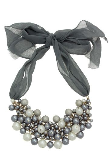 A pearl necklace with layers of grey facet beads, sandblast silver and grey balls. This statement necklace has a ribbon chain for additional texture.