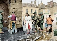 Sainte-Marie-du-Mont, Normandy. A group of American soldiers stand at the village fountain on June 12, 1944. A woman is walking away with two pitchers while three children are watching the scene, and an old man is fetching water next to a GI expected to wash his dishes. Sainte-Marie-du-Mont was liberated by a group of paratroopers of the 501st and 506th Regiments of the 101st Airborne Division.