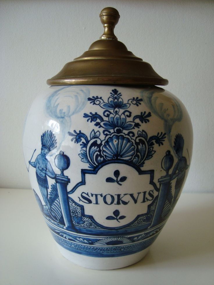 A circa 1750 Dutch Delft blue and white tobacco jar with metal cover Marked MQ (possibly for Quirinus Mesch at de Vier Helden van Rome) Ovoid body with an ogival cartouche inscribed STOKVIS. The cartouche flanked by two Indians smoking the calumet and foliage 27 cm. high (lid included)