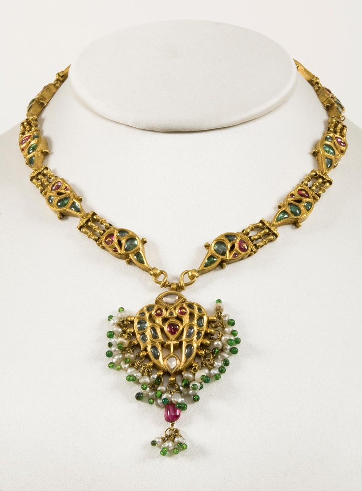 A gold headdress.  India, Rajasthan, 19th century.  Provenance: A gold headdress, set with rubies and emeralds and decorated with suspended pearls and green glass beads
