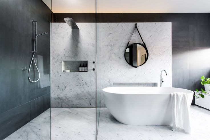 A beautiful blend of marble in a modern minimalist aesthetic. Love the curbless shower and stylish showerhead.