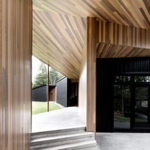 Sprawling Quebec house by Alain Carle  contrasts black brick with warm cedar  - black painted brick mixed well with the darker floorboards and the cedar panelled ceiling. - Brings focus to ceiling instead of floor, unusually. - Will black brick be even hotter than regular brick?