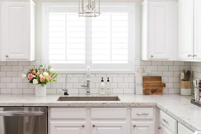 Window With White Frames Inside A Kitchen With A White Subway Tile Arrangement A In 2020 White Subway Tile Kitchen Kitchen Backsplash Designs White Granite Countertops
