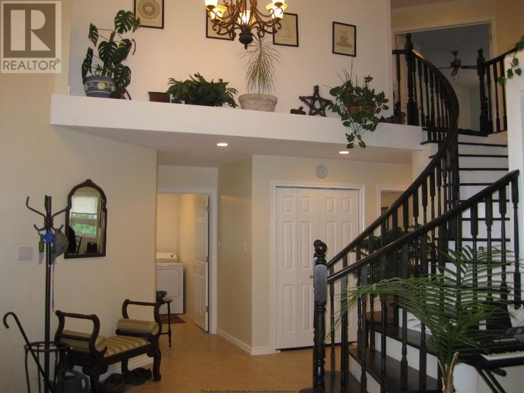 Grand foyer with open staircase, bright with windows & vaulted ceiling over living/dining areas.