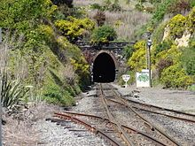 Lyttelton rail tunnel 01.jpg The Lyttelton Rail Tunnel, initially called the Moorhouse Tunnel, links Christchurch with port of Lyttelton in Canterbury. It is the country's oldest operational rail tunnel, & is on one of first railway lines in district. On completion in 1867 it became the first tunnel in the world to be taken through the side of an extinct volcano, and at 2.7 km, the longest in the country. Its opening made the Ferrymead Railway, New Zealand's first public railway line…