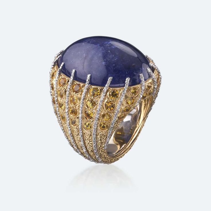 Cocktail ring with purplish blue tanzanite on a mounting with white gold sprigs alternating with yellow gold and diamonds. Among the most splendid and coveted gems, tanzanite is the stone of transmutation, varying its blue from lilac to sapphire to deep purple according to angulation and exposure to light. Tanzanite is the crystal inviting us to spiritual introspection, meditation, communication with the unconscious. It offers protection and health like no other gem…