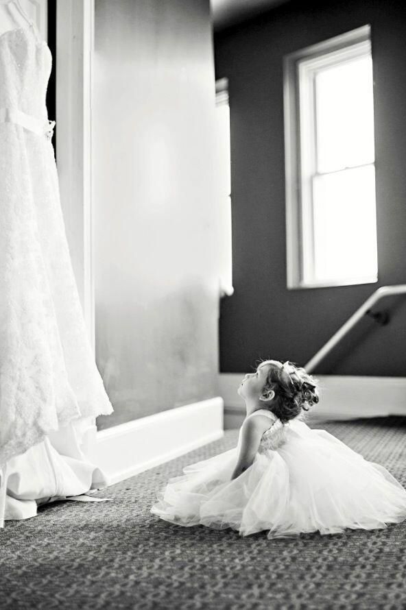 Prewedding shot of flowergirl looking at the dress