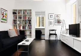 the room is 10m x 5m. white walls. black floors. dark wooden furniture. 1 red wall (can't help myself). black form ply shelving.