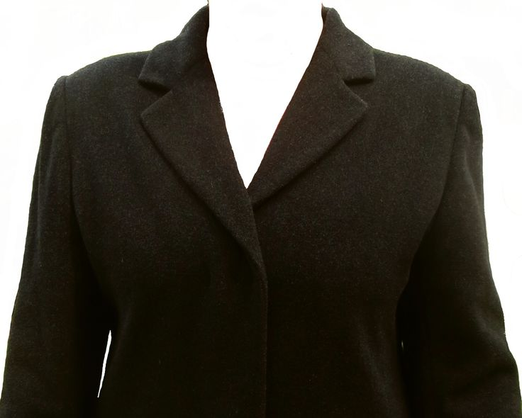 A long slim cut European winter wool coat with a full lining. Two pockets, hidden buttons, padded shoulders, a back flap, excellent quality and in great condition.