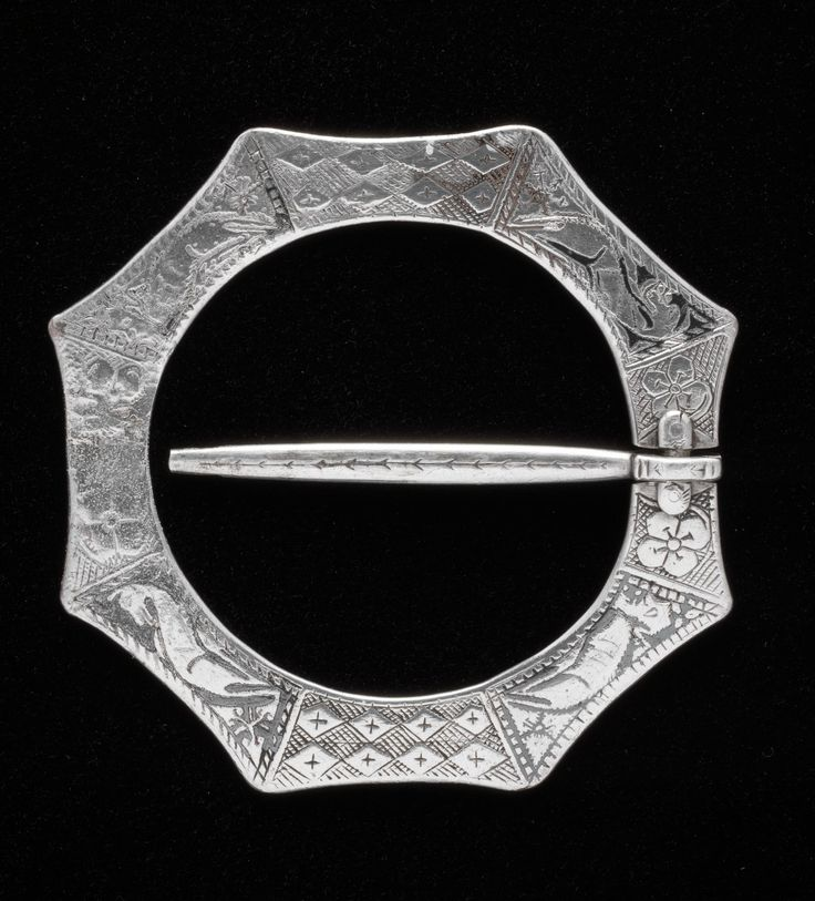 """Octagonal brooch of silver inlaid with niello, decorated with animals, two with human heads, and inscribed """"?IHSN ANAN"""", from Kilmore, Mull"""