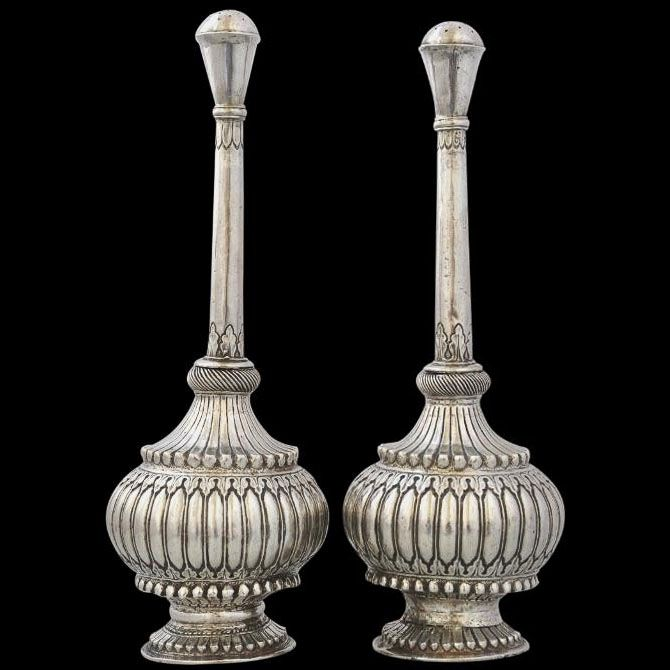 View 1: This fine pair of early silver rosewater sprinklers have heavily gadrooned, bulbous bodies; flared feet; long, thin necks chased with acanthus leaf and petal borders; and flared, pierced nozzles.