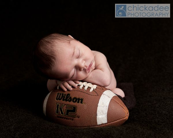 Newborn baby boy asleep on a football by chickadee photography www chickadee photo