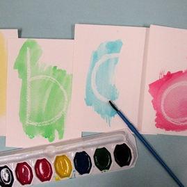 met witte wasco de letters schrijven, dan met verf de letter te voorschijn toveren