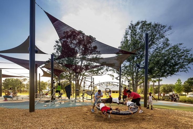 Lakefront Park, Kissimmee Florida, United States. Parents give their all in spinning their kids on a new piece of playground equipment. AECOM provided landscape architecture and planning services for the new park linking the downtown area to the lakefront.   Photo © Robb Williamson / AECOM