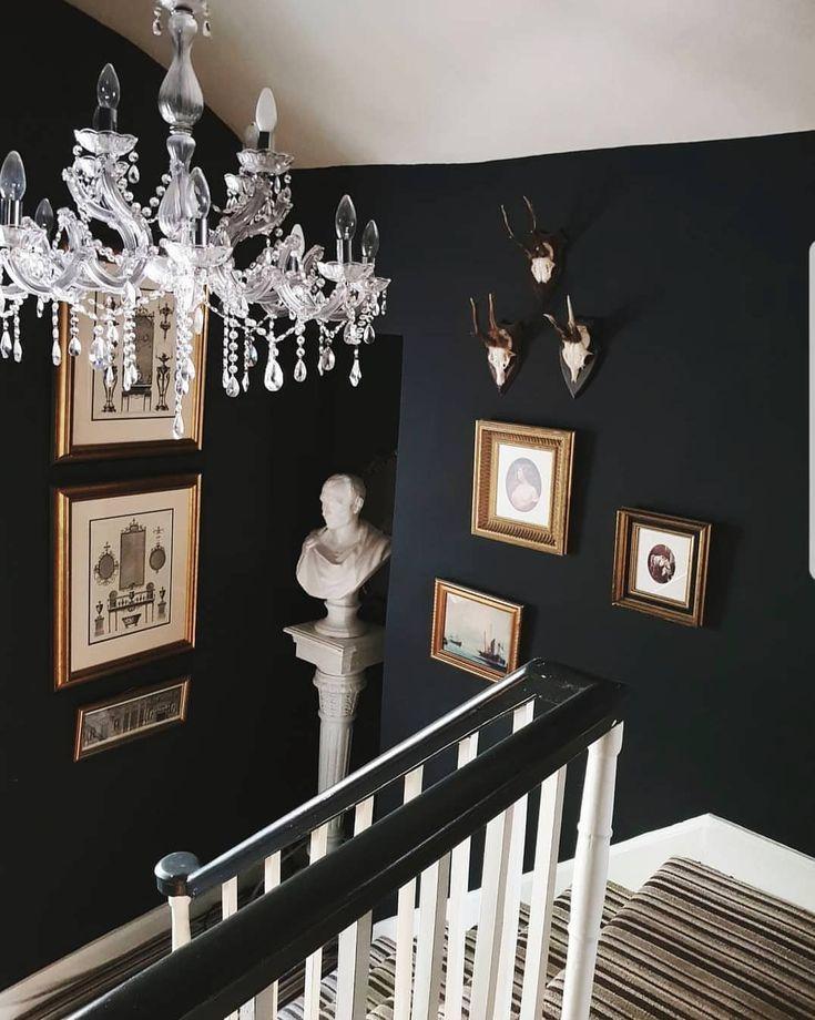 art display, stairs, dark walls, chandelier, striped carpet, bust