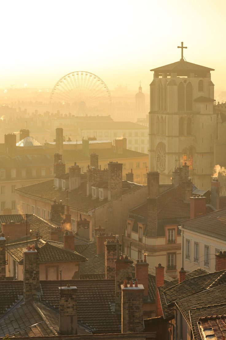 The big wheel - Cathedral Saint-Jean-Baptiste in Vieux Lyon and the Ferris wheel at Place Bellecour in Lyon during a foggy sunrise in december.