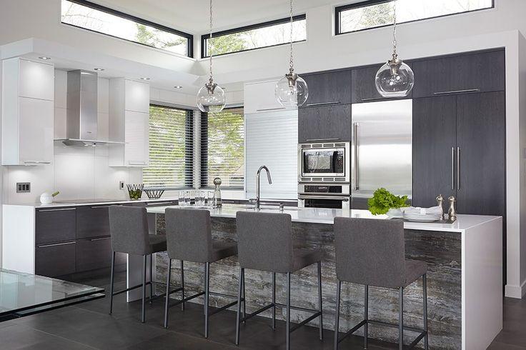 Les armoires de cette cuisine lumineuse et contemporaine, ont été fabriqués avec un mariage de thermoplastique blanc et chêne teint. Comptoir en quartz.