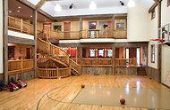 "This 10,000sq ft ""sports barn"" was built for the owner's 25 grandchildren and features ""his-and-hers bunkrooms, a full kitchen and a bar, ...a basketball court with a scoreboard, a bowling lane and an electronic golf simulator. The movie theater has leather seating for 30. The stage is equipped with professional lighting and sound systems, operated from a balcony above.""  Crazy cool!"