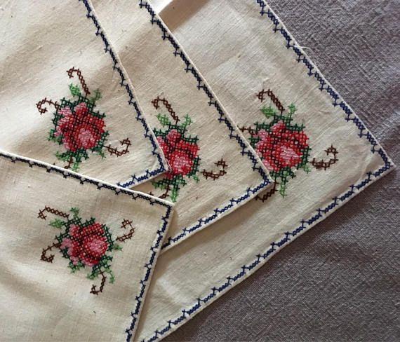 Jolie broderies serviettes de table des années 1950 ou plus tôt. Un ensemble de 4 serviettes de table, chacun d'eux a une rose brodée et un bord bleu, travaillé en point de croix. Ils sont en excellent état. Imprimé sur un tissu de type toile de coton/lin.  Chaque rond de