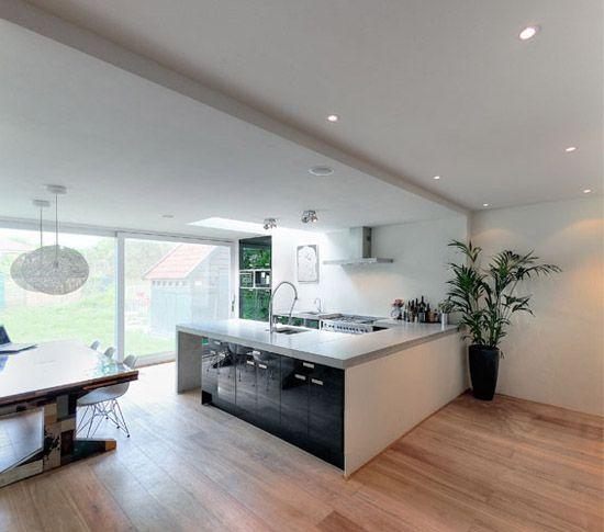 Verbouwing met uitbouw te Amstelveen. In de uitbouw een zwarte keuken met betonnen aanrechtblad.