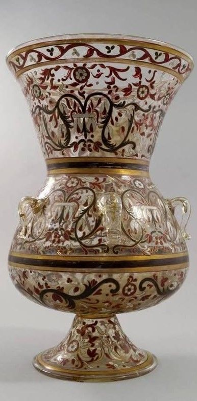 A Rare Mamluk style gilt and enamelled glass Mosque lamp, Europe, 19th century, of typical form with sloping round body and a flared mouth on a short base, six applied hanging loops, overall decorated with scrolling foliage, 37.5 cm high.