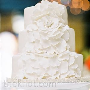 Feminine sugar-flower petals cascaded down the three-tiered fondant cake.
