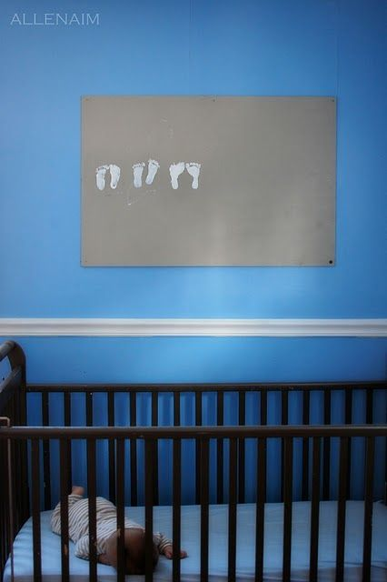 """LOVE this!!! """"I have kept footprints of my older boys in books, but with the youngest, I decided to make a little bit of cheap art with them.  I took a free piece of plywood and painted it with leftover neutral paint.  I painted my kiddos feet with white paint and *very carefully* placed the footprints on the board.  Every few months I make another set and watch his feet """"grow"""""""