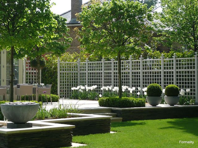 Gorgeous Portuguese limestone terrace with trellis privacy screen and buxus clipped topiary balls