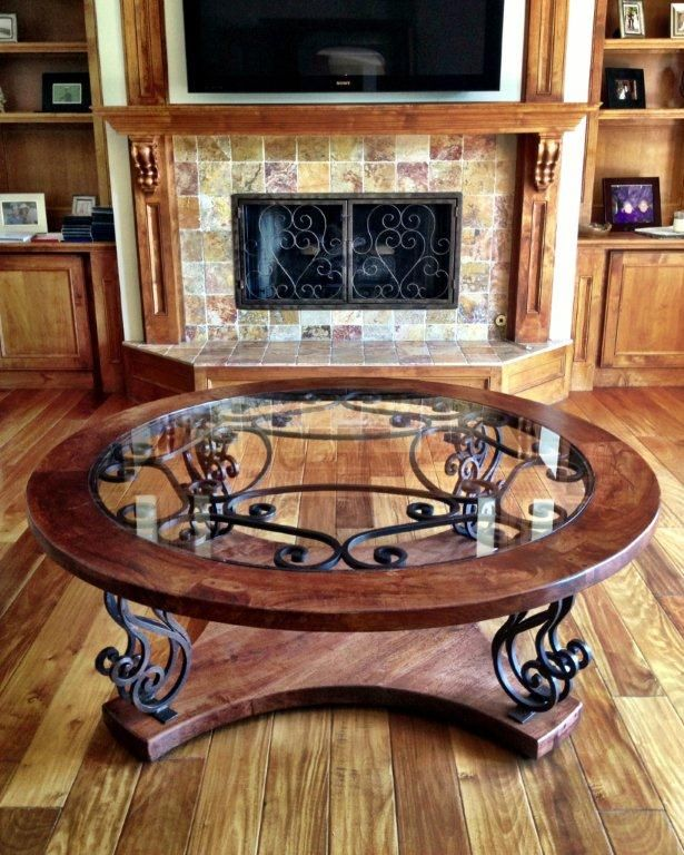 This custom coffee table showcases solid mesquite wood with beautiful hand forged wrought iron designs seen in a rounded-glass top and serving as four legs.