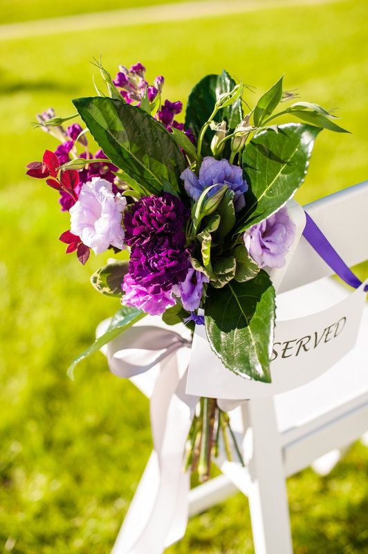 pew markers for an outdoor wedding are clutches of purple lisianthus, purple carnations, lemon leaf and purple stock ties to the chairs with pale grey ribbon.