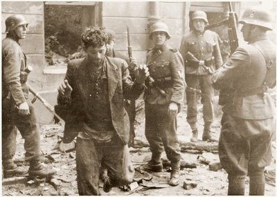 SS assault troops capture two Jewish resistance fighters pulled from a bunker during the suppression of the Warsaw Ghetto Uprising. The original German caption reads alternately: Pulled from a bunker or Bandits.