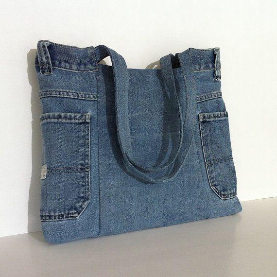 Reciclar un pantalón de jean azul claro e hizo este bonito bolso de mano. , Cosía y tachonada de pequeños trozos de arpillera con bordes con flecos en la parte delantera para añadir un bonito adorno. Está totalmente forrado con una tela de la impresión de algodón, cuenta con 2 fuera y 3 bolsillos interiores. Un broche de imán mantiene cerrado. Puedes llevar carpetas, libros o computadora portátil en este bolso durable.  Medidas: width:15(38cm) Centro height:12(30cm) Depth:2(5cm)…