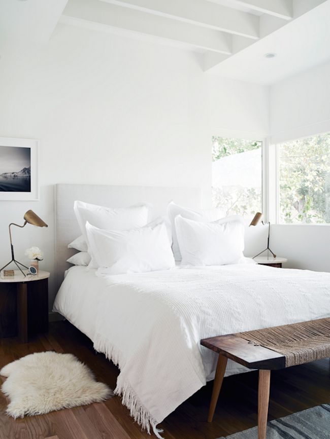 White bedroom, featuring a canvas headboard, white linens, a wooden and twine bench, and bronze lighting | The Kinfolk Home